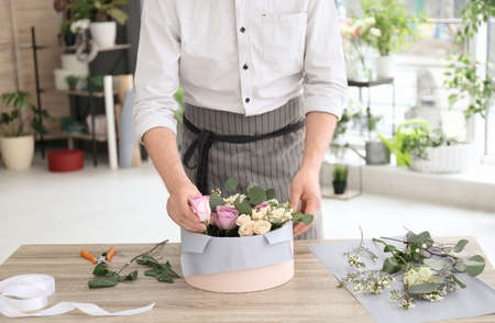 Male florist creating floral composition at workplace