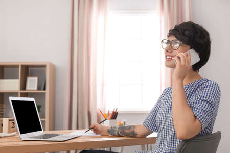 Young woman talking on mobile phone while working at desk. Home office