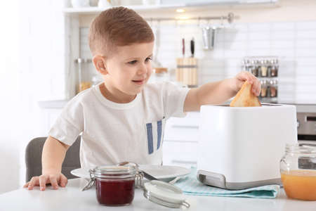 Cute little boy preparing toast with sweet jam at table Archivio Fotografico