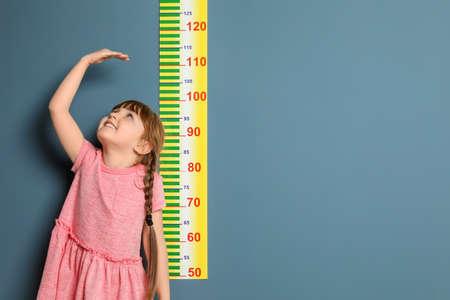 Bambina che misura la sua altezza sul colore di sfondo