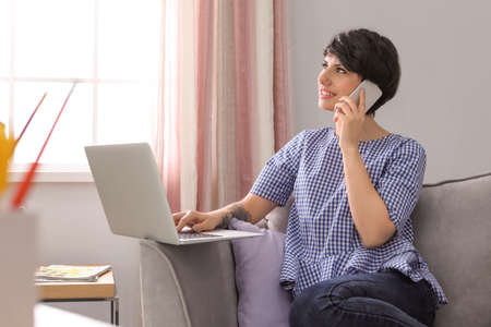 Young woman talking on mobile phone while working with laptop at home