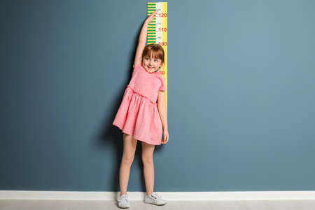 Little girl measuring her height near color wall Stock Photo