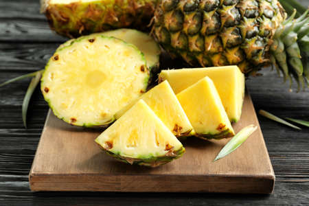 Fresh sliced pineapple on wooden board, closeup Imagens