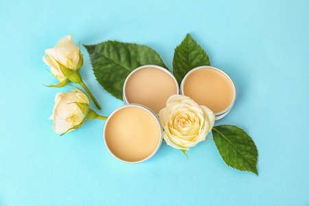 Hygienic lip balms and flowers on color background 写真素材