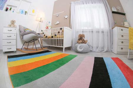 Interior de habitación de bebé acogedor con cuna y mecedora Foto de archivo