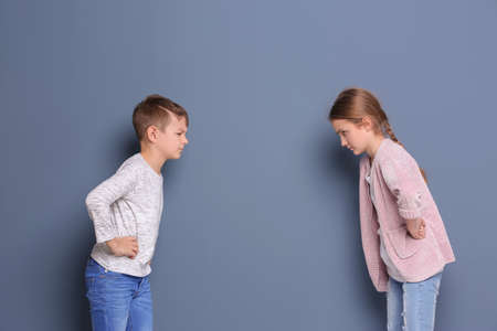 Brother arguing with sister on color background