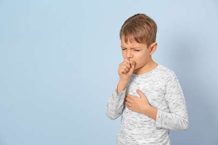 Little boy coughing on light background