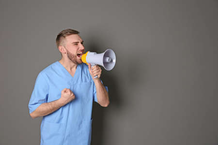 Male doctor shouting into megaphone on grey background