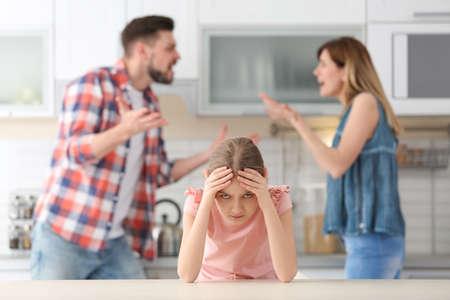 Niña infeliz sentada en la mesa mientras los padres discuten en la cocina Foto de archivo