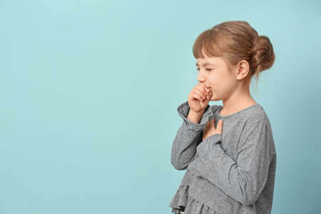 Little girl coughing on color background
