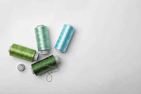 Hilos de coser de color y dedal sobre fondo blanco, vista superior