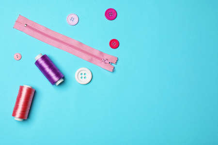 Flat lay composition with sewing threads on color background