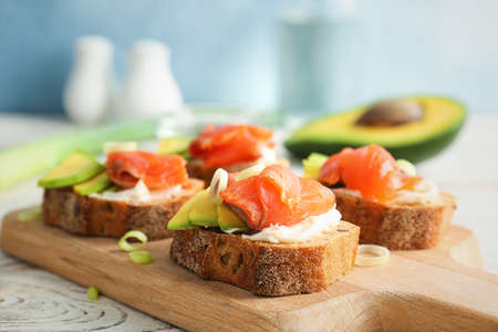 Tasty sandwiches with fresh sliced salmon fillet and avocado on wooden board, closeup