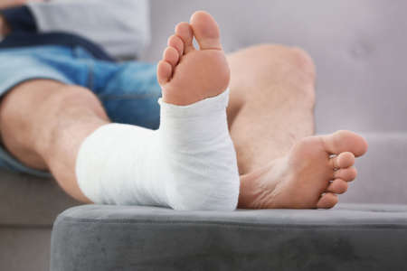 Jeune homme avec une jambe cassée en plâtre assis sur un canapé à la maison Banque d'images