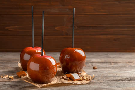 Delicious red caramel apples on table