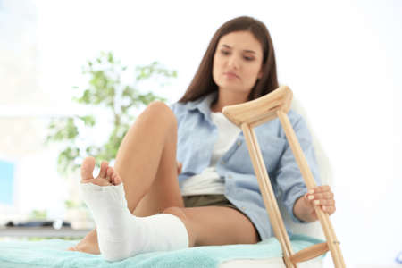 Woman with broken leg in cast on couch