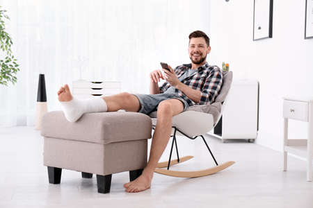 Man with broken leg in cast using mobile phone while sitting in armchair at home