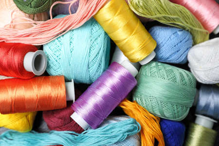 Different sewing threads as background Фото со стока