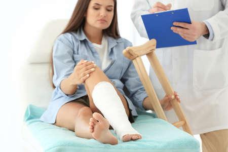 Vrouw met gebroken been in gegoten op bank Stockfoto