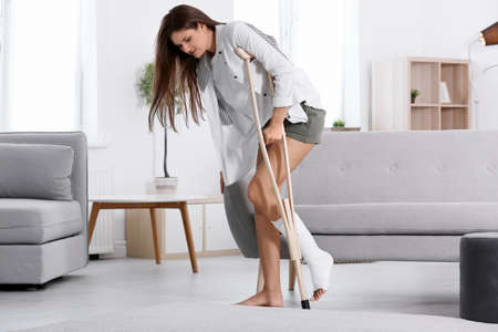 Young woman with crutch and broken leg in cast at home 스톡 콘텐츠
