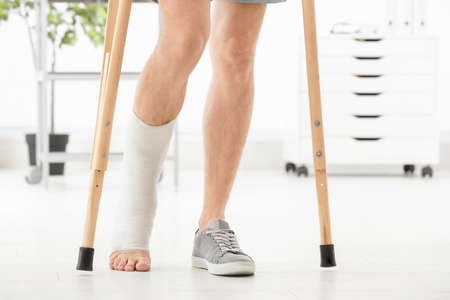 Man with broken leg in cast standing on crutches, indoors
