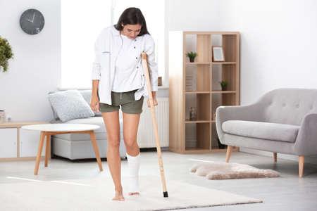 Mujer joven con muleta y pierna rota en yeso en casa