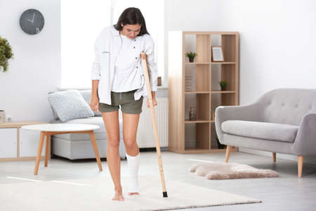Young woman with crutch and broken leg in cast at home Foto de archivo