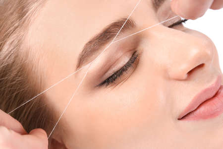 Young woman having professional eyebrow correction procedure in beauty salon Standard-Bild - 105462936