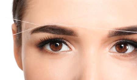 Mujer joven corregir la forma de las cejas con hilo, primer plano