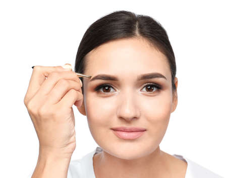 Young woman plucking eyebrow with tweezers on white background