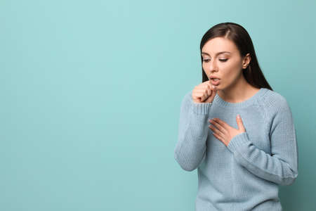 Young woman coughing on color background