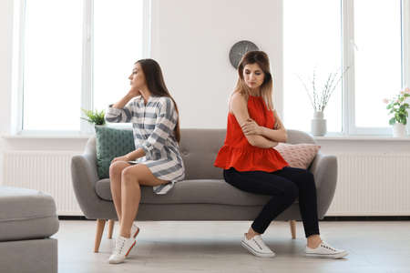 Women sitting on sofa after arguing at home Stock Photo