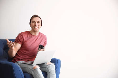 Young blogger with laptop sitting in armchair against light wall Фото со стока