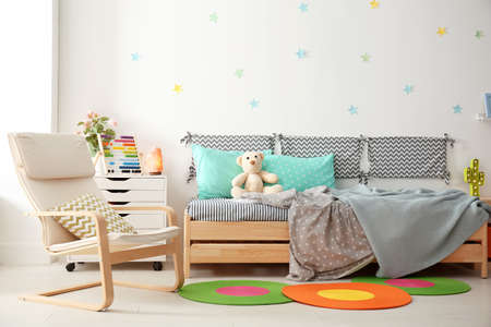 Modern child room interior with comfortable bed and armchair