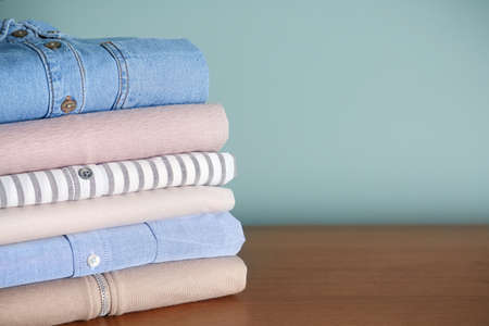 Stack of clothes on table against grey background