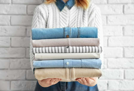 Woman holding stack of clean clothes near brick wall