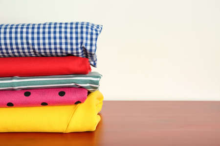 Stack of clothes on table against light background Stockfoto