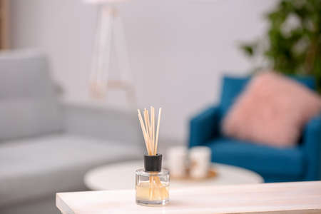 Handmade reed freshener on table against blurred background