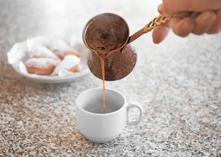 Mujer vertiendo café aromático en la taza en la mesa