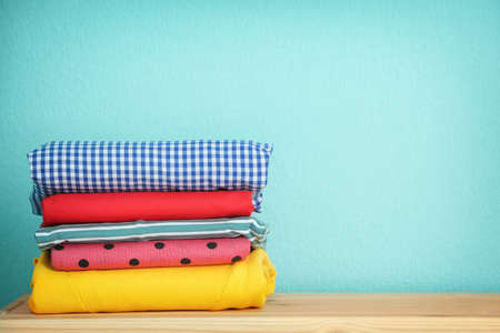 Stack of clean clothes on table against color background Stockfoto