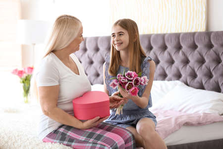 Happy mature woman receiving bouquet and gift from her teenage granddaughter at home 写真素材