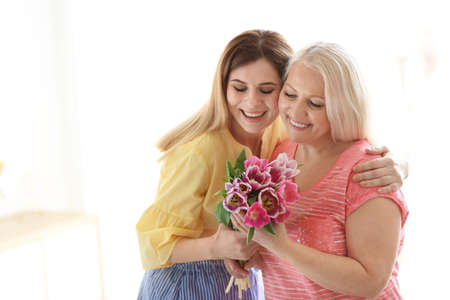 Daughter congratulating happy mature woman on Mother's Day at home Foto de archivo