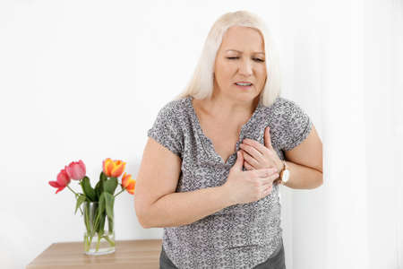 Mature woman having heart attack at home Stockfoto