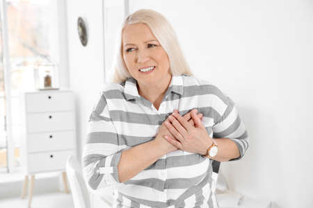 Mature woman having heart attack at home Foto de archivo