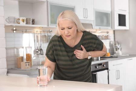 Mujer madura con un ataque al corazón en la cocina