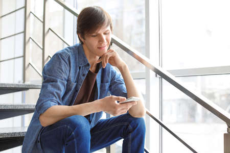 Portrait of confident young man with mobile phone on stairs 写真素材