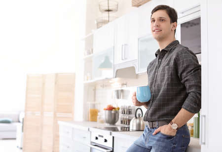 Portrait of confident young man with cup in kitchen
