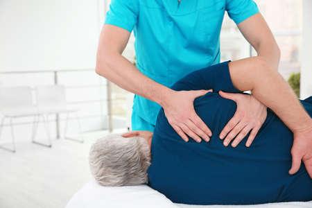 Junger Physiotherapeut, der mit älteren Patienten in der Klinik arbeitet Standard-Bild