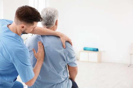 Fisioterapeuta joven que trabaja con el paciente senior en la clínica