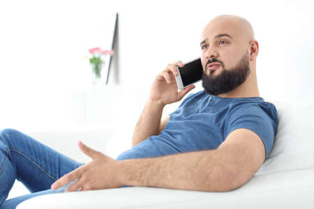 Portrait of young man talking on mobile phone on sofa 写真素材